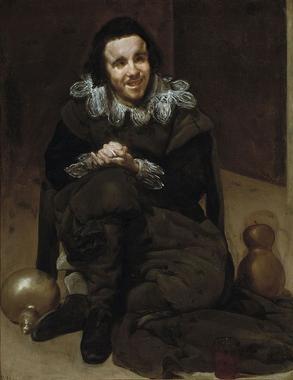 Un homme assis par terre, visiblement handicapé, souriant ...